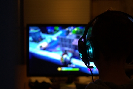 Silhouette of a person in front of a screen with a headset on. Playing the game Fortnite.