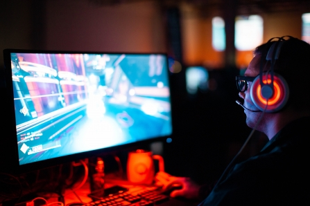 A person sat wearing headphones, gaming on a PC monitor